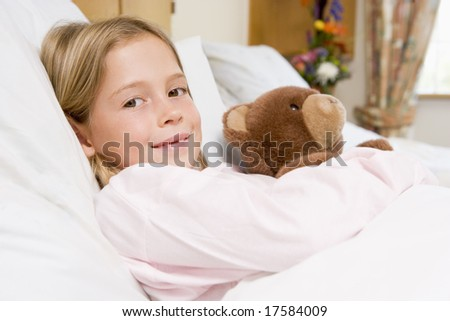Young Girl Lying In Hospital Bed,Holding Teddy Bear - stock photo