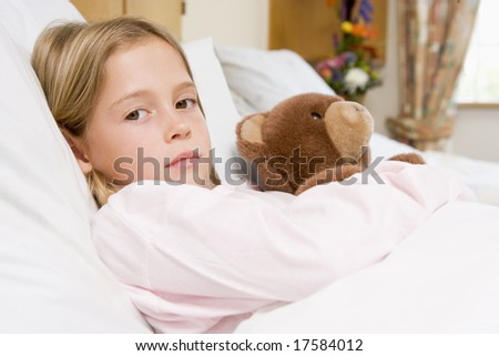 Young Girl Lying In Hospital Bed With Teddy Bear - stock photo