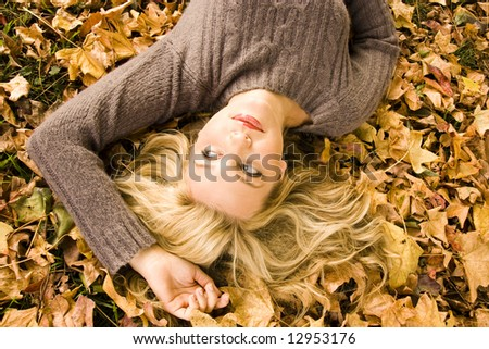 young girl lying in the autumn leaves at the park - stock photo