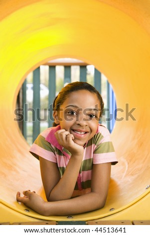 Young girl lying in yellow crawl tube at playground and smiling. - stock photo