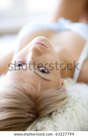 Young girl lying, looking at camera, natural light from window