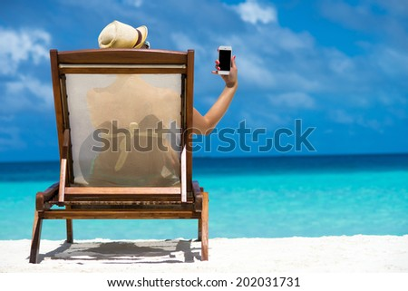 Young girl lying on a beach lounger with mobile telephone in hand on the tropical island  - stock photo