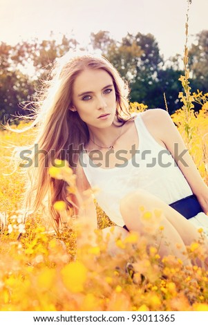young girl lying on a flower glade - stock photo