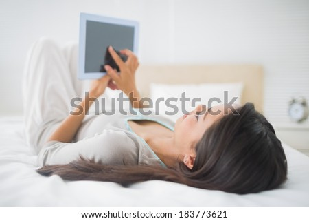 Young girl lying on bed looking at her tablet pc in her bedroom at home