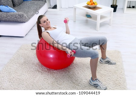 Young girl lying on fitness ball and exercising with dumbbells