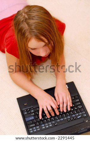 Young girl lying on the floor with portable computer