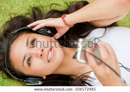Young girl lying on the grass and listening player