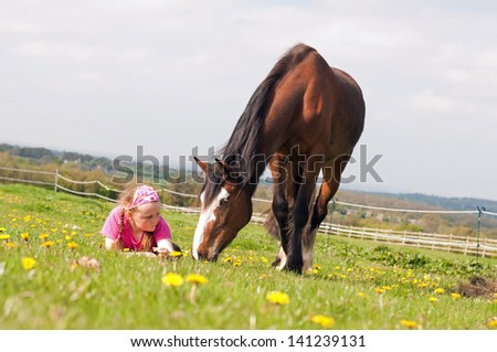 Young girl lying on the grass while her horse grazes - stock photo