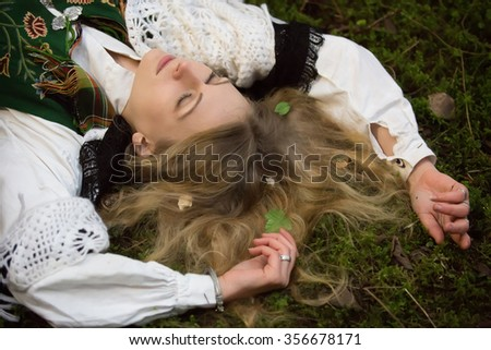 Young girl lying on the ground in the forest - stock photo