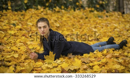 Young girl lying on the leaves in the autumn park. - stock photo