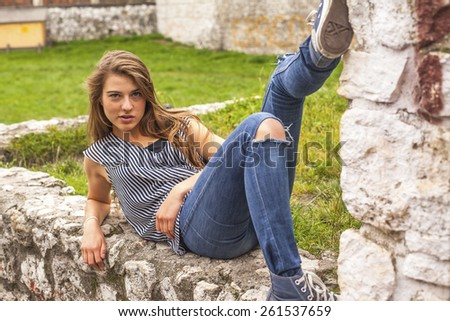 Young girl lying on the stone curb in a city park.