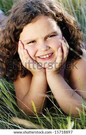 Young girl lying outdoors smiling - stock photo