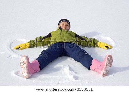 Young Girl Makes a Snow Angel - stock photo
