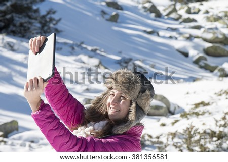 Young girl makes selfie photos with a tablet in the mountains in winter