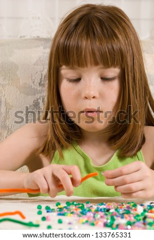 Young girl making a bead bracelet - stock photo