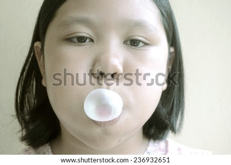 young girl making a bubble from a chewing gum (in monotone color) - stock photo