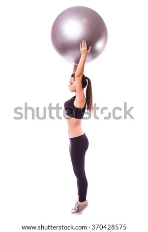 Young girl making exercise with pilates ball, against white background