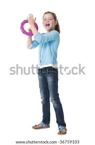 Young girl making music with tambourine on white background