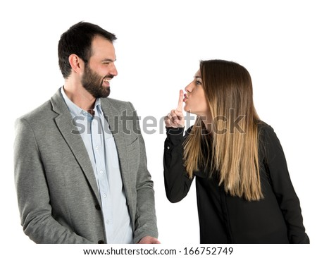 Young girl making silence gesture at her boyfriend over white background