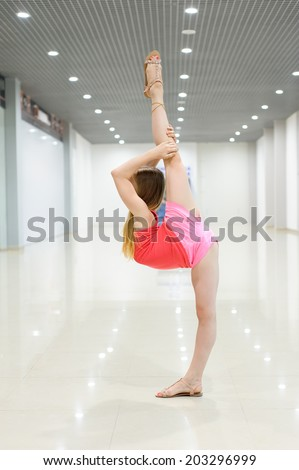 Young girl making vertical split in big light room