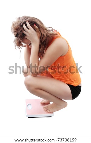 young girl measures her weight with the weights - stock photo