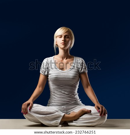 Young girl meditating in half lotus. - stock photo