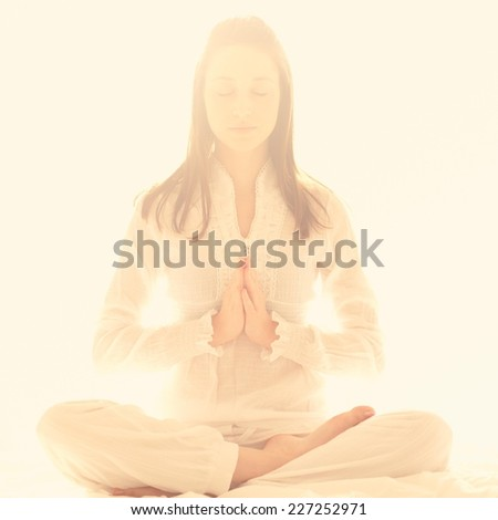 Young girl meditating in half lotus - light background, copy space. - stock photo