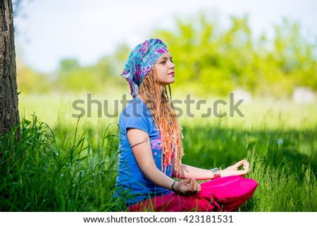 Young girl meditating in the park. Girl with pigtails in a turban meditating sitting on the grass on a sunny day - stock photo