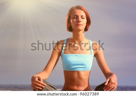 young girl meditating on beach - stock photo
