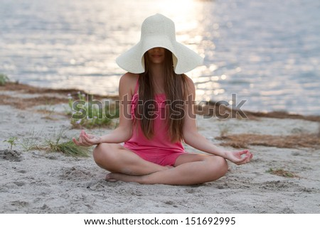 Young girl meditating on the beach - stock photo