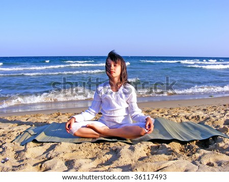 Young girl- meditating on the beach - stock photo