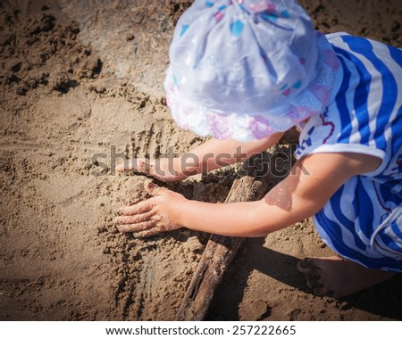 Young girl molds of sand on the beach. - stock photo