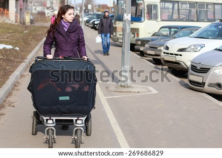 young girl-mother walking with twins in a stroller - stock photo