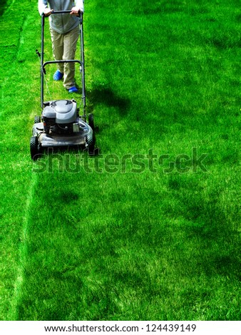 Young Girl Mowing green grass lawn with push mower - stock photo