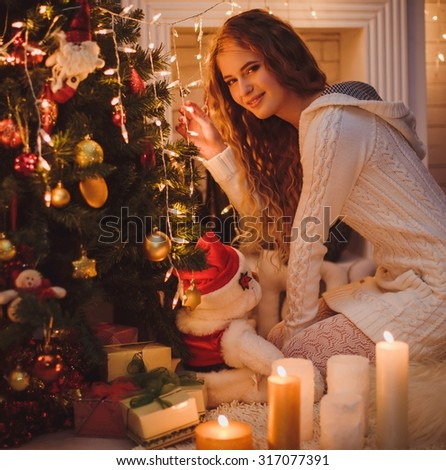 Young girl near a new-year tree with gifts and candles - stock photo