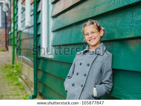 Young girl near green wooden wall looking at the camera