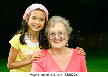 Young girl of mix ethnicity with her grandmother enjoying each other's company, outdoor in the park. - stock photo