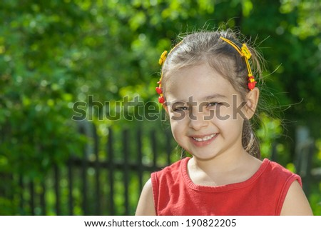 Young girl of preschool age against green lawn with fence - stock photo
