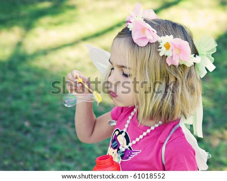 Young girl of 4 years wearing fairy wings and blowing bubbles in the park.