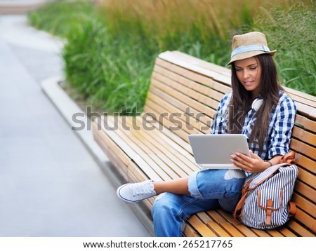 Young girl on a bench with a laptop - stock photo