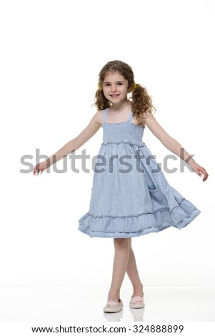 Young girl on a bicycle with a white background. She is smiling at the camera and wearing casual clothing. - stock photo