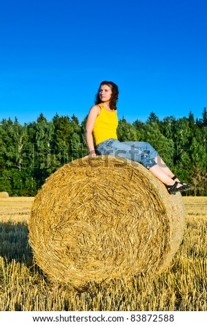 young girl on a haystack in a field - stock photo