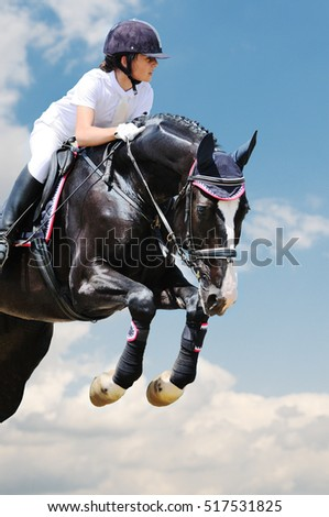Young girl on black horse in jumping show