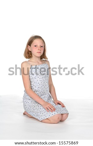 young girl on knees with sad expression on her face