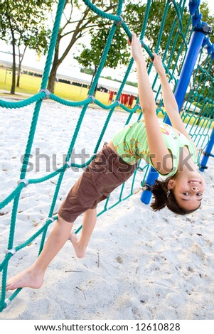 Young girl on rope climbing activity in playground - stock photo