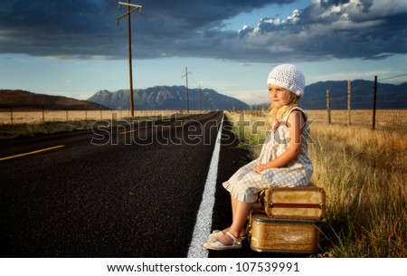 Young girl on side of road with vintage suitcases in a mountain landscape