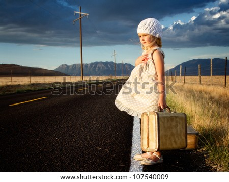 Young girl on side of road with vintage suitcases in a mountain landscape - stock photo