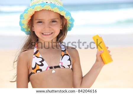 Young girl on the beach holding suncream - stock photo