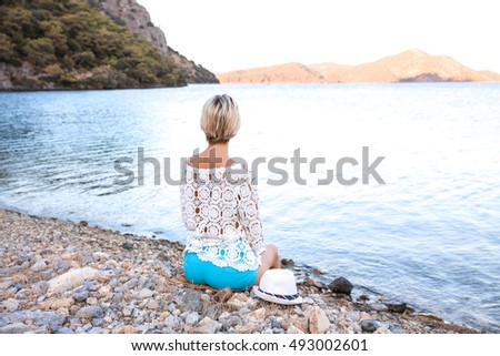 Young girl on the beach of stones; she looks at the sea; vacation time; the mountains to the sea; relaxation concept