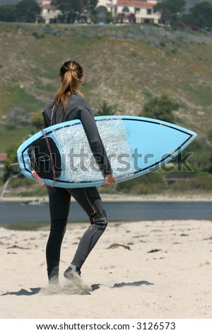 Young girl on the beach ready for surfing in California - stock photo